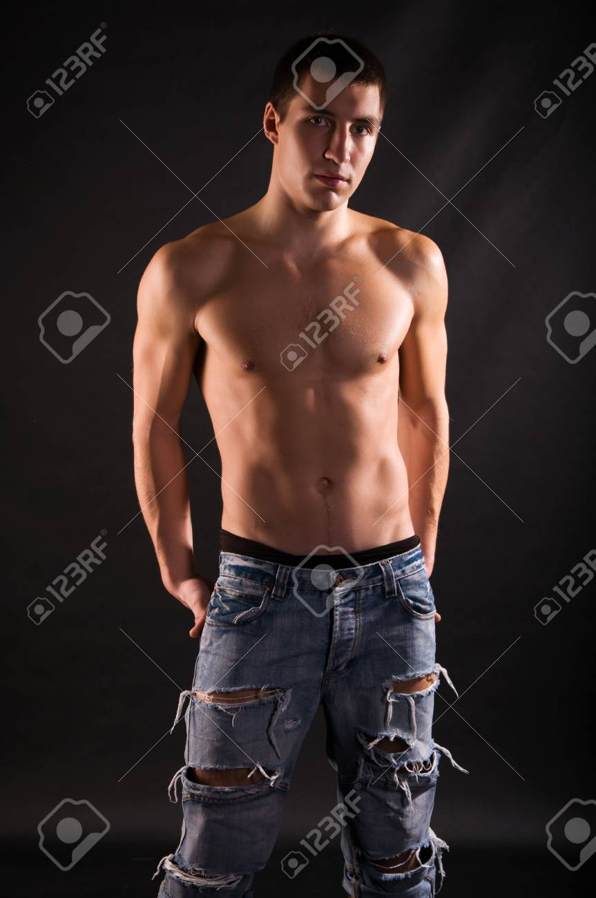 Dramatic light photo of muscular young man in front of black background Stock Photo - 6807283