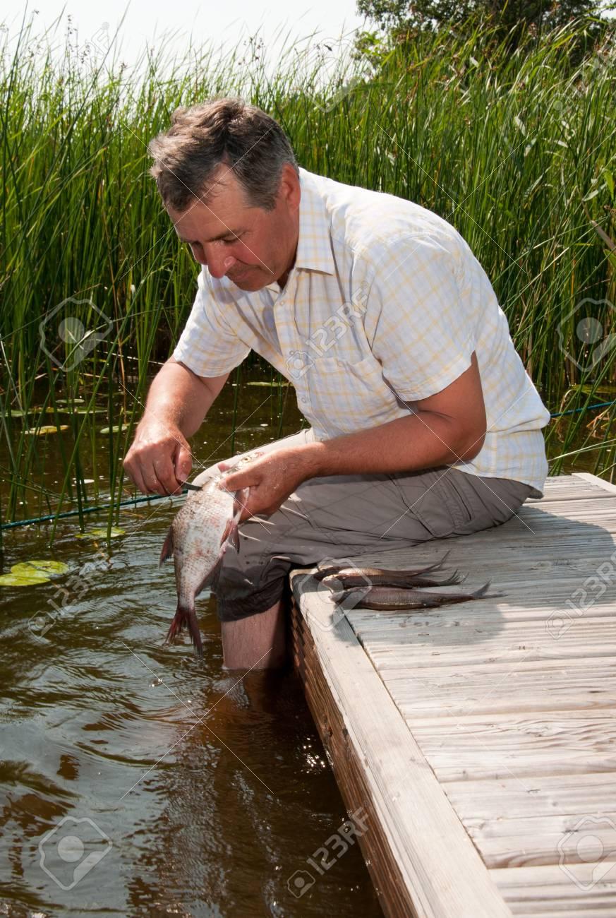 Senior man scaling fish Stock Photo - 8341344