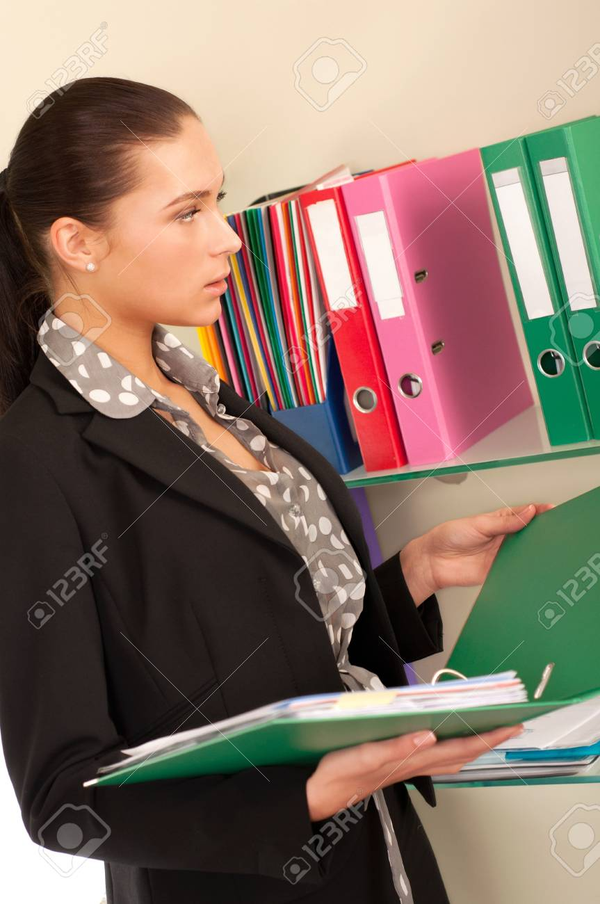Business woman in front of shelves with folders Stock Photo - 11854373
