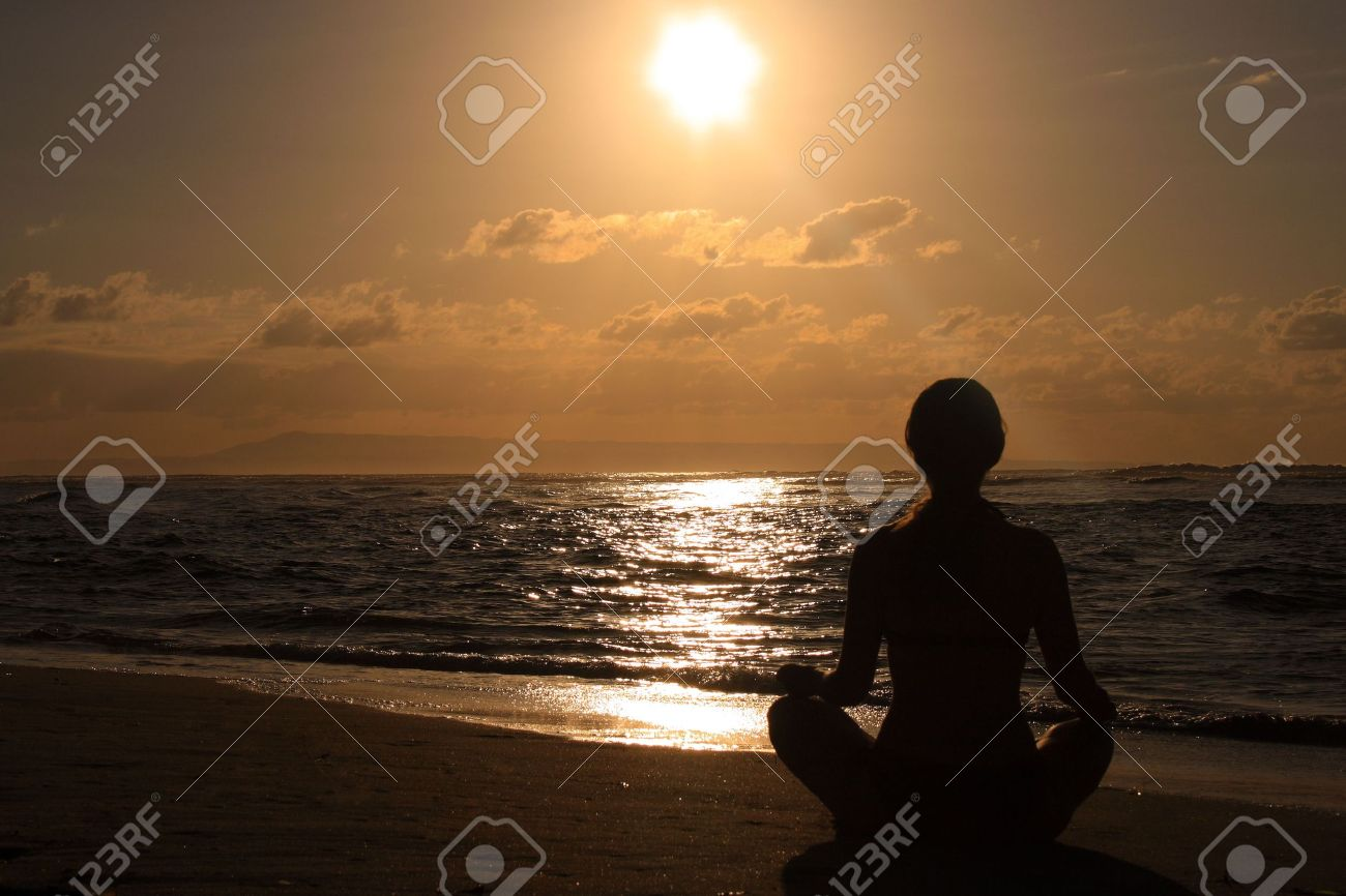 Female meditating on the beach in the morning  at sunrise Stock Photo - 1780118