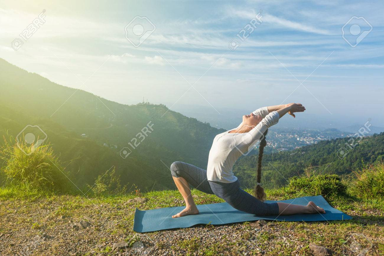 Sporty fit woman practices yoga Anjaneyasana - low crescent lunge pose outdoors in mountains in morning - 46880038