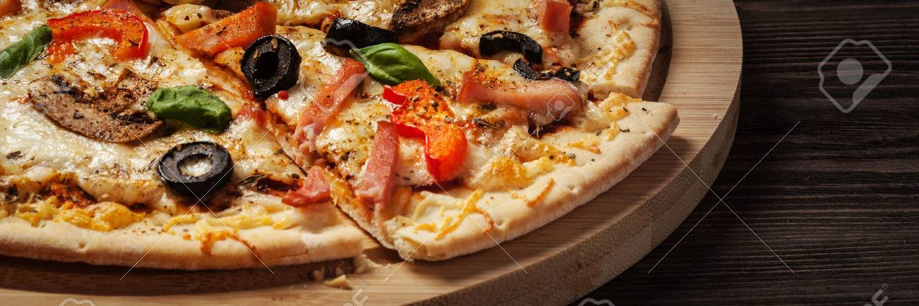 Letterbox panorama of sliced ham pizza with capsicum and olives on wooden board on table - 47718388
