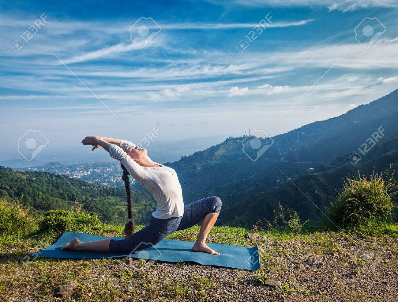 Sporty fit woman practices yoga Anjaneyasana - low crescent lunge pose outdoors in mountains in morning - 48366876