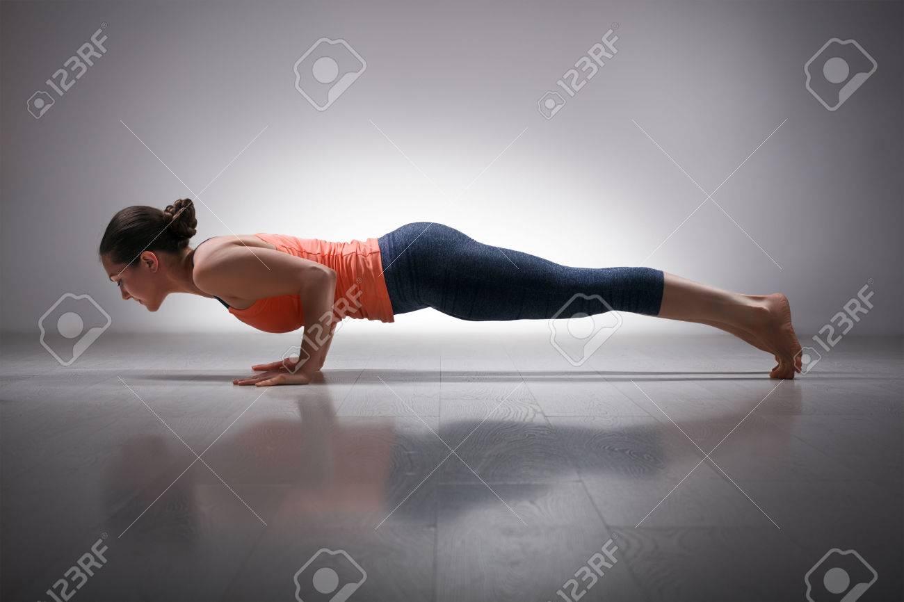 Beautiful sporty fit woman practices Ashtanga Vinyasa yoga Surya Namaskar Sun Salutation asana Chaturanga Dandasana - four-limbed staff pose - 48777299