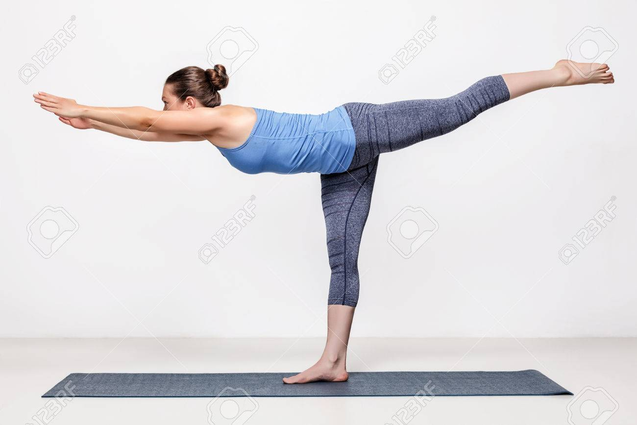 Beautiful sporty fit woman practices yoga asana Virabhadrasana 3 - warrior 3 pose - 49248761