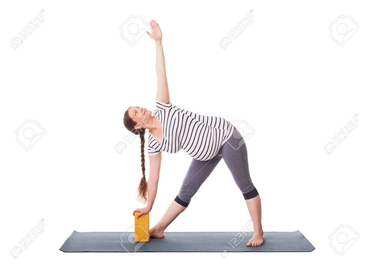 Pregnancy yoga exercise - pregnant woman doing asana Utthita trikonasana - extended triangle pose with block isolated on white background - 60025703
