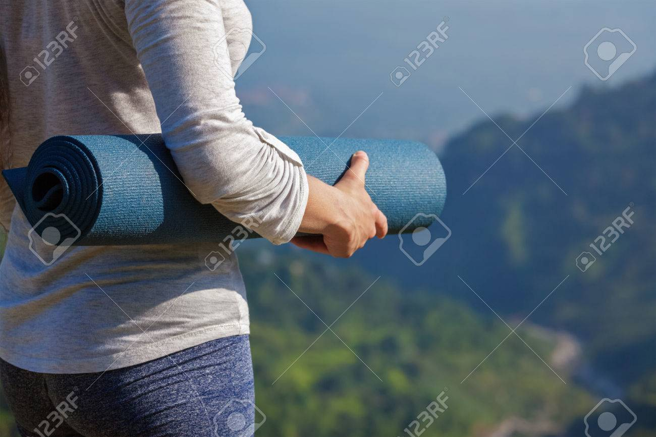 Woman standing with yoga mat outdoors in mountains close up with copyspace getting ready for yoga exercise - 63043170