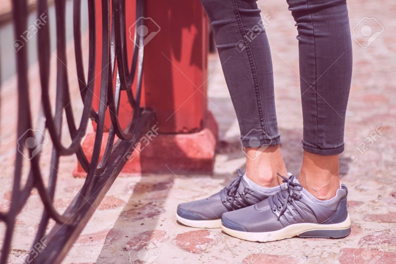 Carretera Y Los Zapatos Jóvenes Zapatillas Deportivas Las En Vaqueros Cerca De Pantalones Caminando La VallaOcio Pie Metal Chicas Estilo rshQCtdx