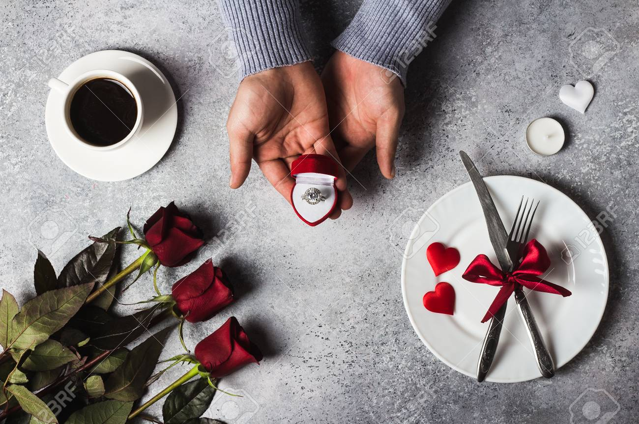 Stock Photo - Valentines day romantic dinner table setting man hand holding engagement ring in box marry me wedding with red rose gift surprise on grey ... & Valentines Day Romantic Dinner Table Setting Man Hand Holding ...