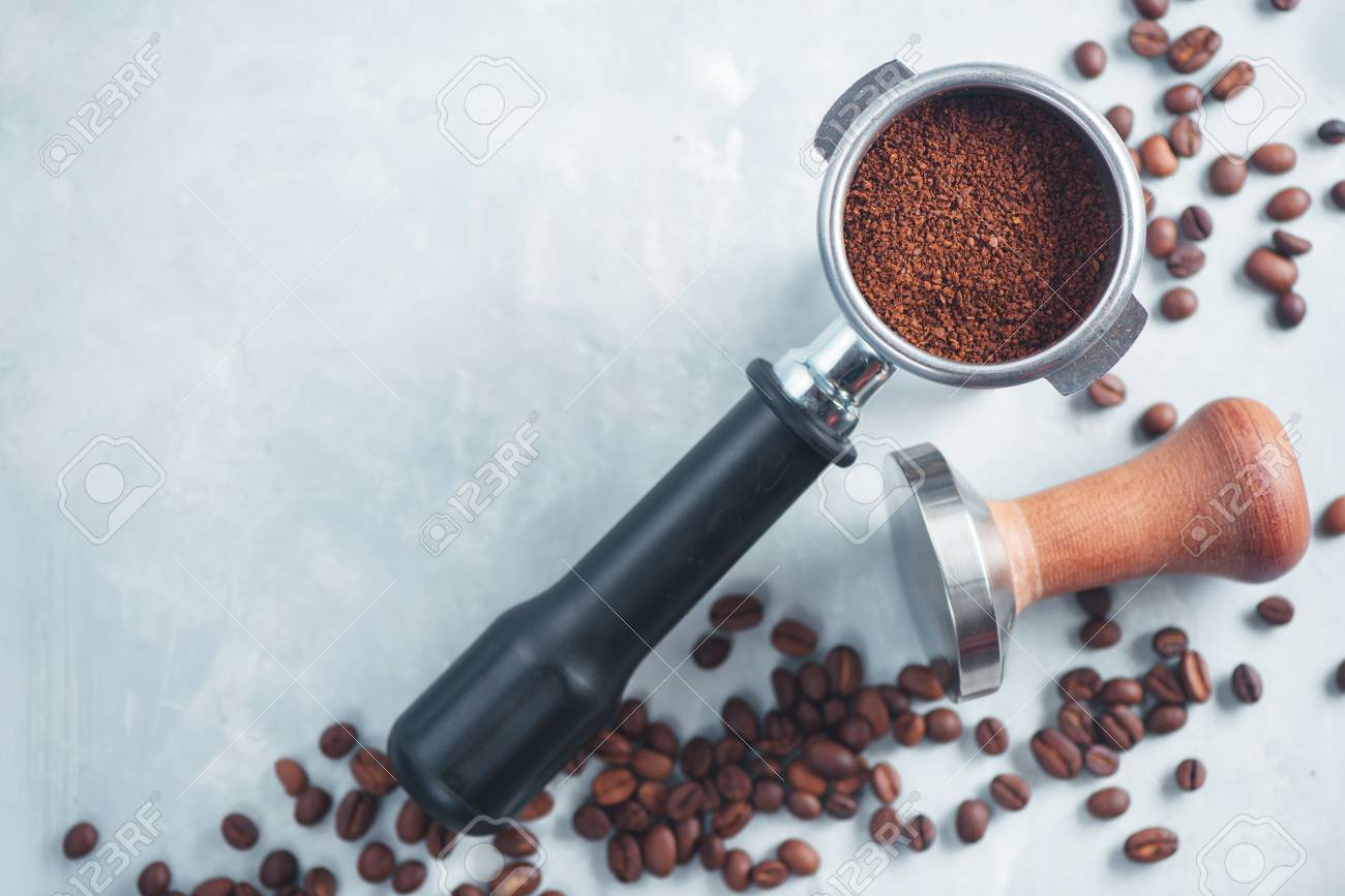 Portafilter with ground coffee close-up. Equipment for brewing coffee flat lay on a light background with copy space. - 95829461
