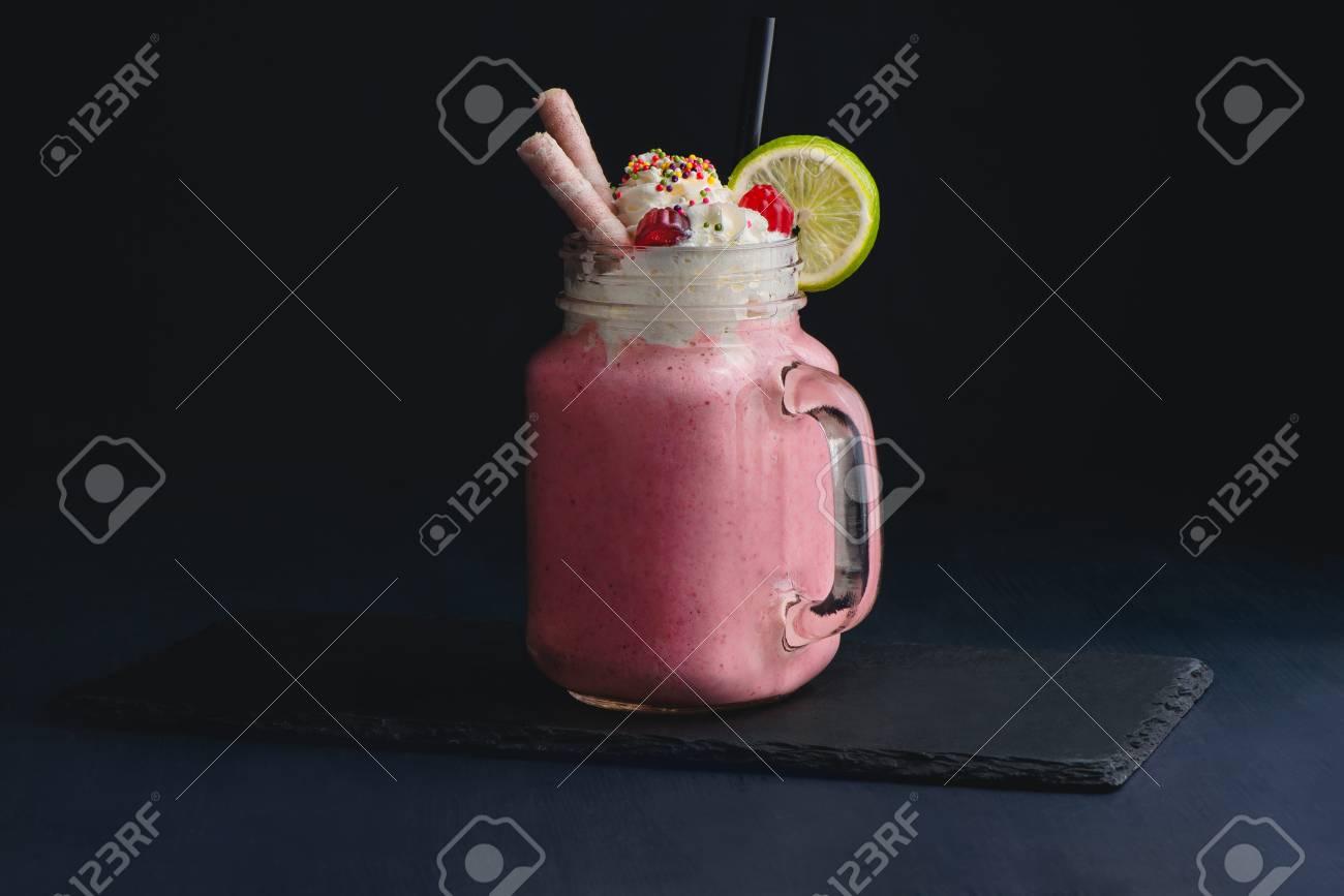 Cold strawberry milkshake in a vintage glass mason jar. Dark background with copy space for a menu. - 113171400