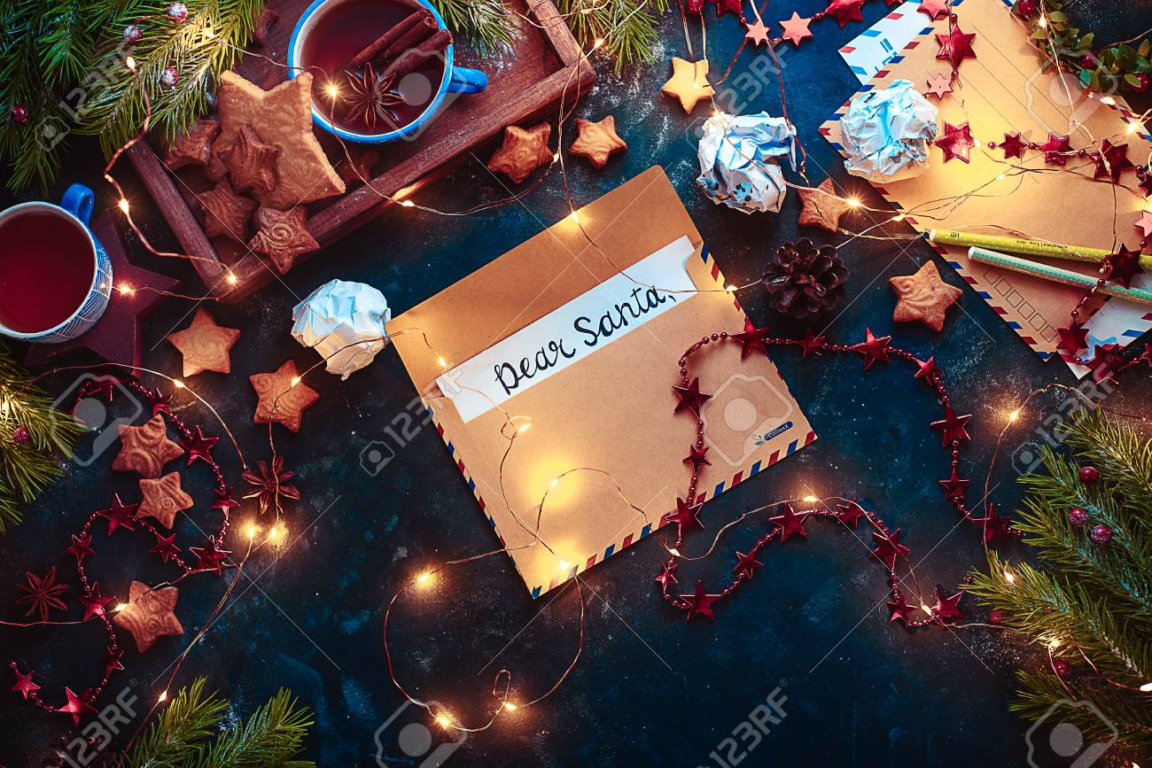 Letters to Santa concept, Christmas flat lay with fairy lights, star-shaped cookies, and tea. Christmas still life from above with contrast colors and copy space - 113245517