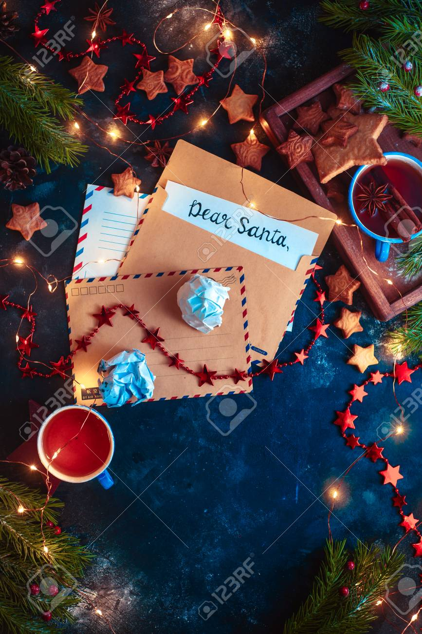 Letters to Santa concept, Christmas flat lay with fairy lights, star-shaped cookies, and tea. Christmas still life from above with contrast colors and copy space - 113245518