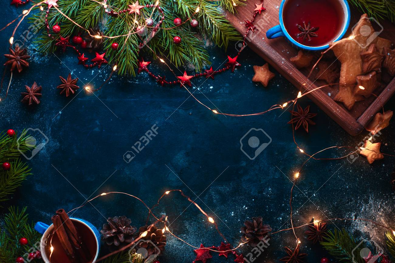 Cookies, tea and fairy lights flat lay with fir tree branches, wooden tray, anise stars, and decorations. Warm winter concept with copy space - 113245523