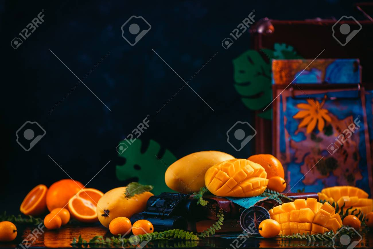 Mango, oranges, kumquat and other tropical fruits on a dark background with copy space. Traveling for the discovery of exotic fruits concept. - 114729892
