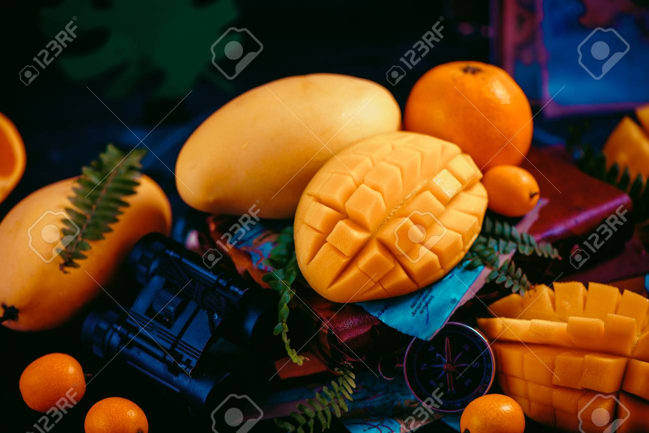 Mango close-up with oranges, kumquat, and other tropical fruits. Dark background with copy space. Traveling and discovery of exotic fruits concept. - 114729897