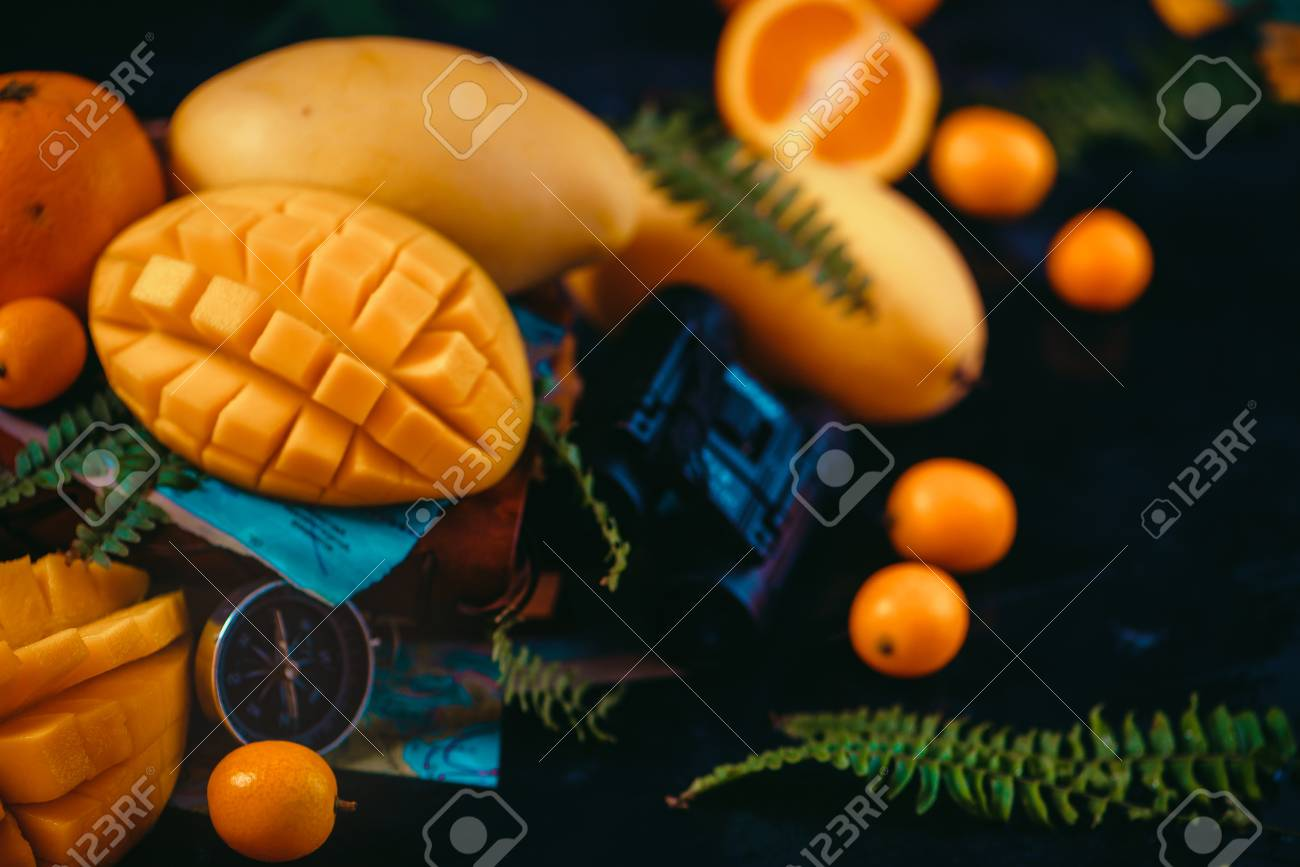 Cut mango halves close-up header with oranges, kumquat, and other tropical fruits. Dark background with copy space. Discovery of exotic fruits concept. - 114729905