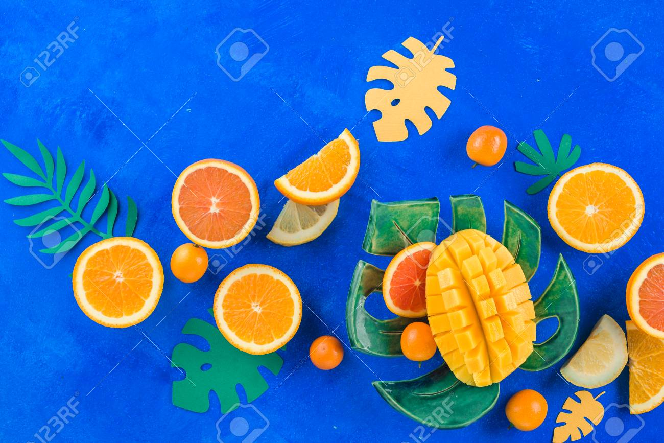 Exotic fruits flat lay. Mango, oranges, kumquat and other tropical fruits on a monstera plate. Bright blue background with copy space. - 114729910