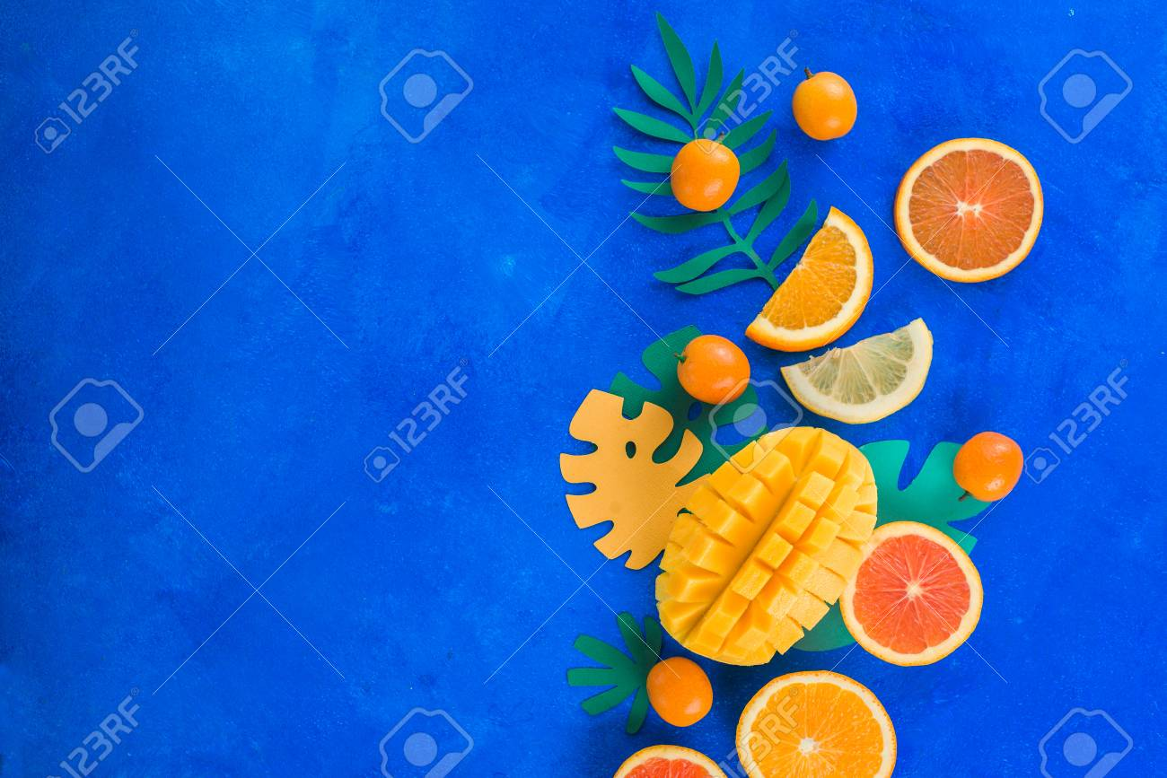 Tropic fruits on a vibrant blue background with copy space. Mango, oranges, kumquat, and other exotic fruits. - 114729917