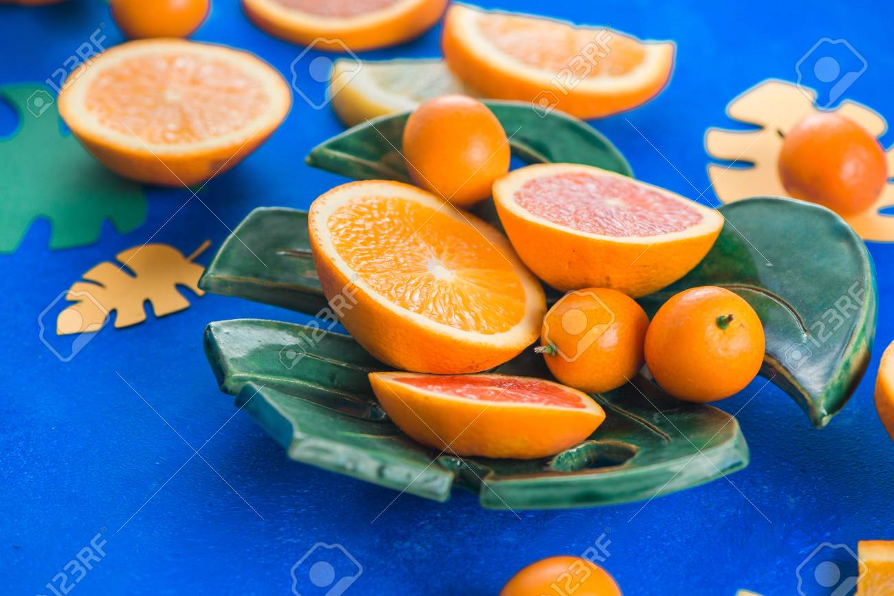 Mango, oranges, kumquat and other tropical fruits on a monstera plate. Bright blue background with copy space. Exotic food header. - 114729958