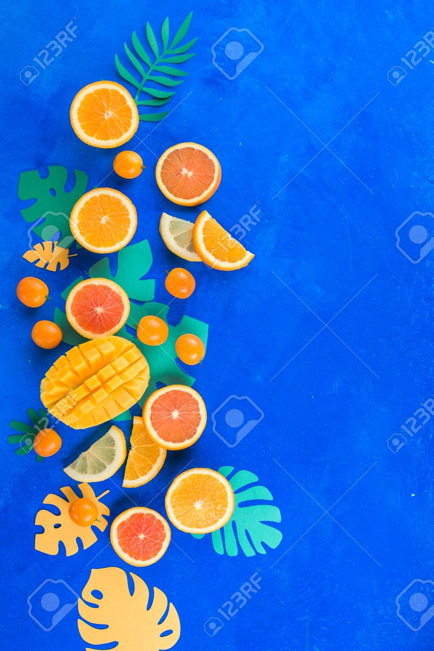 Citrus fruits, mango, oranges, kumquat, and other tropical fruits vibrant blue background with copy space. Exotic fruits close-up. - 114729961