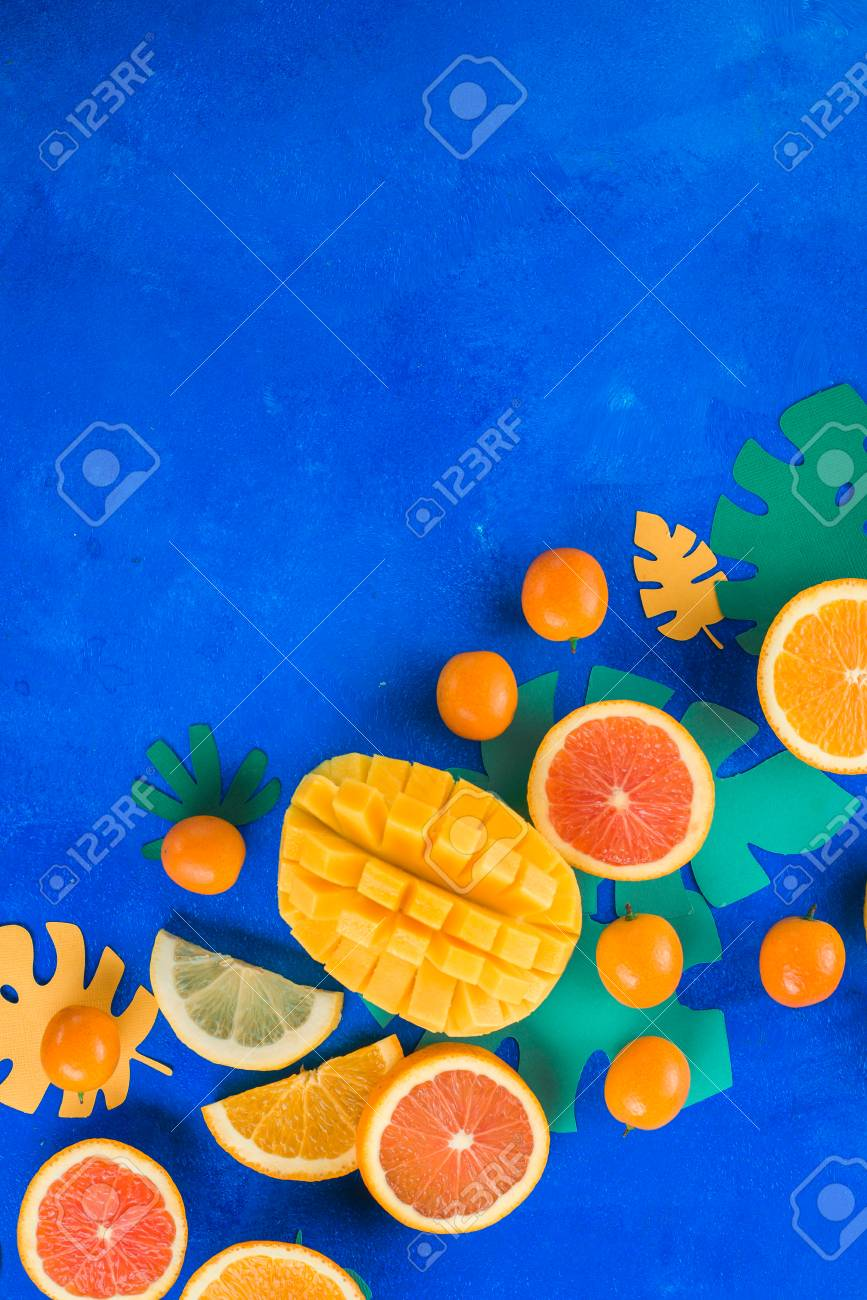 Tropic fruits on a vibrant blue background with copy space. Mango, oranges, kumquat, and other exotic fruits. - 114729964