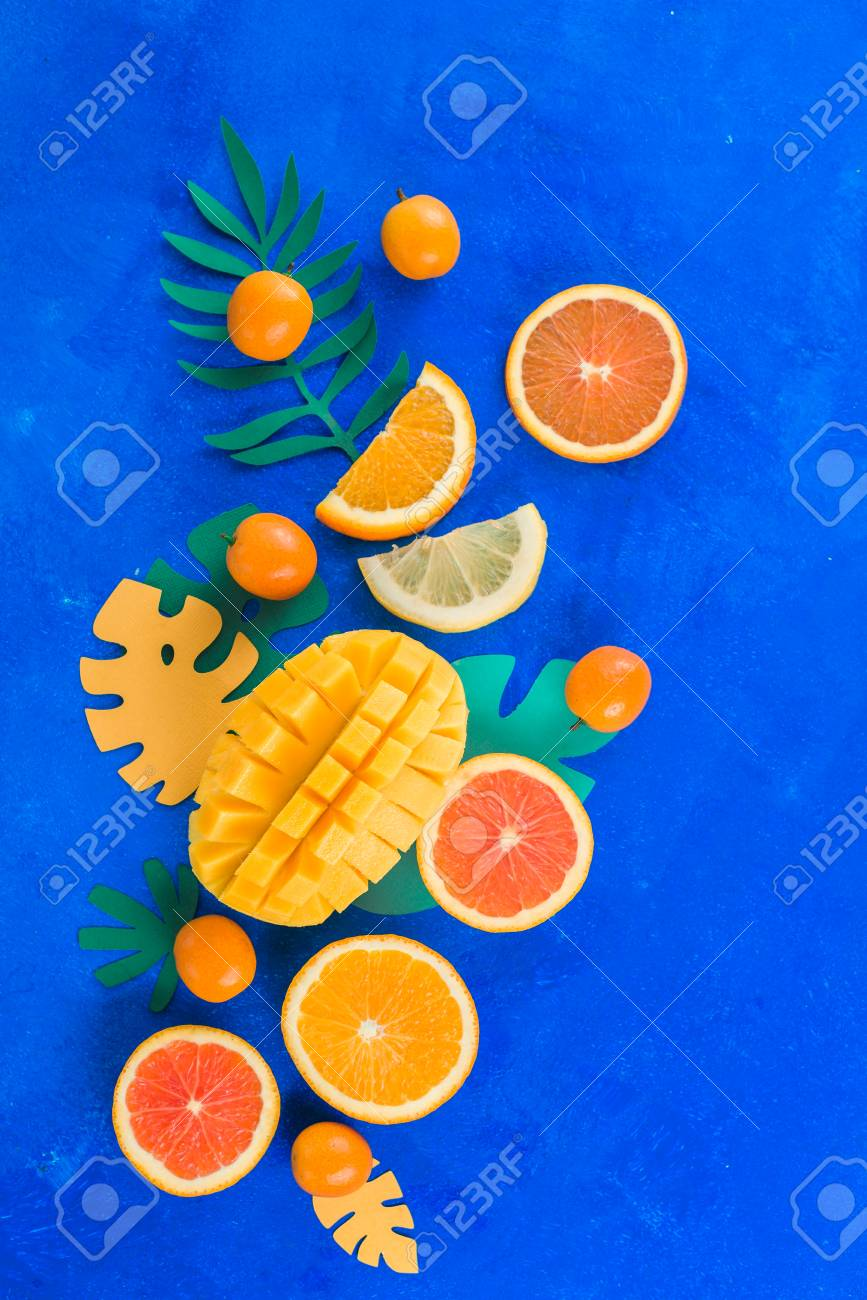 Citrus fruits, mango, oranges, kumquat, and other tropical fruits vibrant blue background with copy space. Exotic fruits close-up. - 114729966