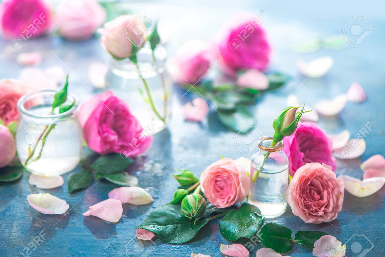 Glass bottles with pink peony roses on a light background with copy space. Feminine header with petals and flowers in pastel tones - 114729985