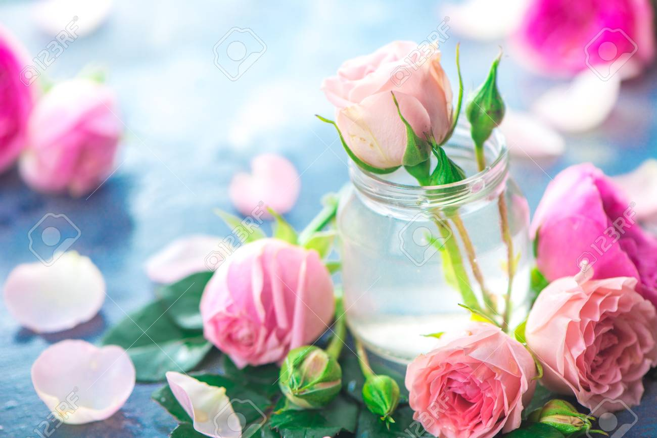 Glass bottles with pink peony roses on a light background with copy space. Feminine header with petals and flowers in pastel tones - 114730019