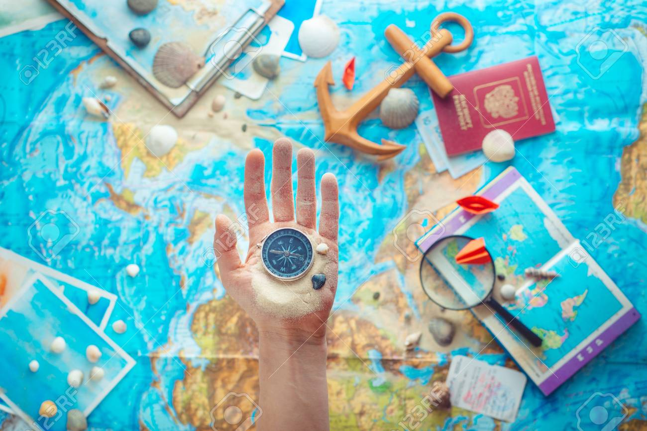Hand holding a compass above map with wooden anchor, paper airplanes, passport and a magnifying glass. Adventure flat lay with copy space - 115930591