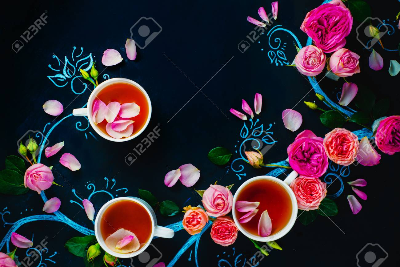 Teacups and flower petals in chalk tree flat lay. Rose tea creative flat lay on a dark background with copy space - 114915061