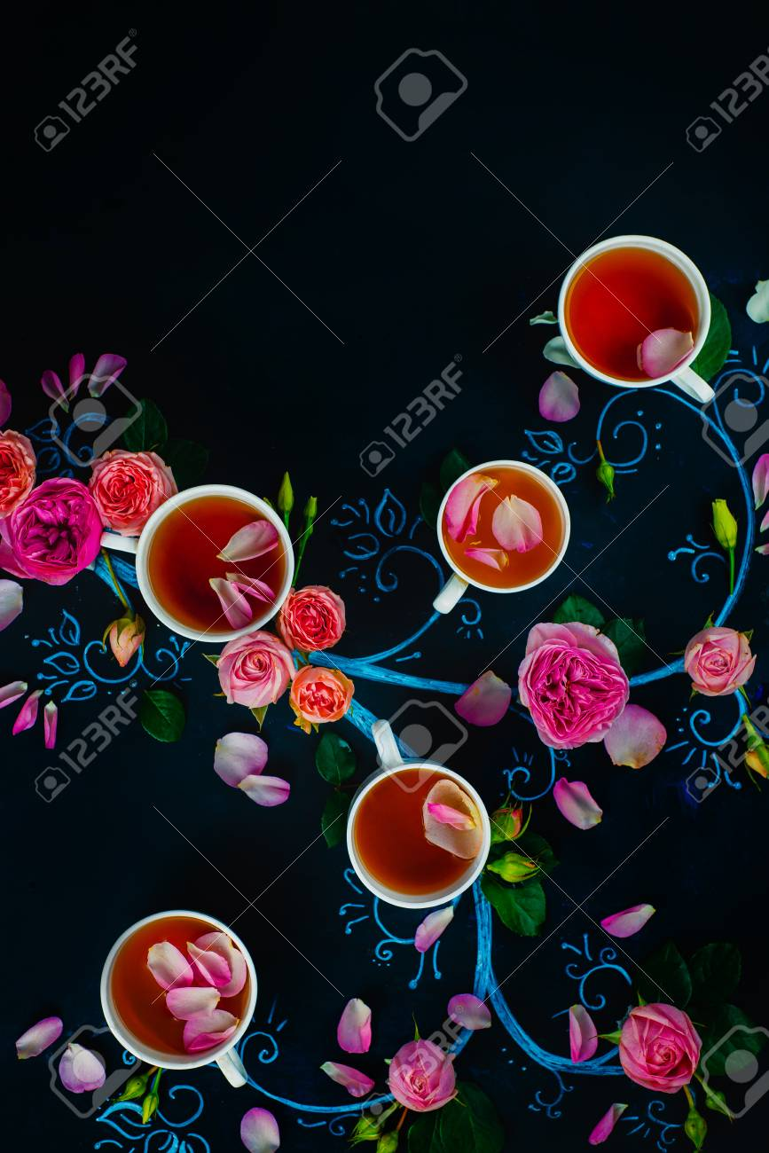 Teacups and flower petals in chalk tree flat lay. Rose tea creative flat lay on a dark background with copy space - 114915084