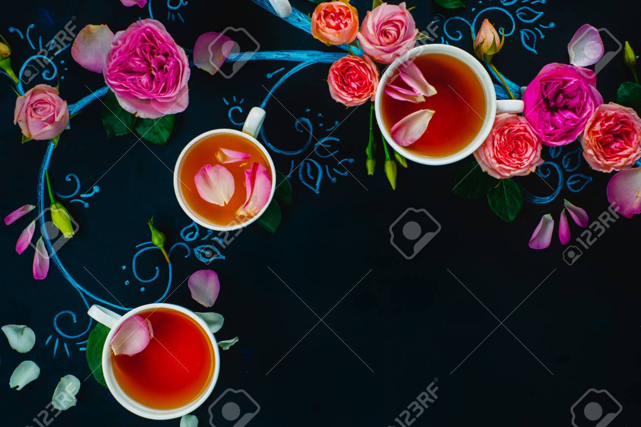 Teacups and flower petals in chalk tree flat lay. Rose tea creative flat lay on a dark background with copy space - 114915087
