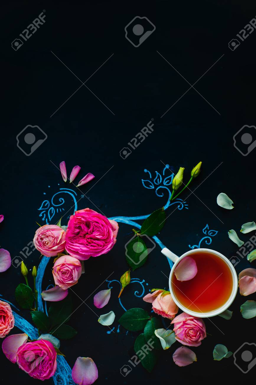 Teacups and flower petals in chalk tree flat lay. Rose tea creative flat lay on a dark background with copy space - 114915107