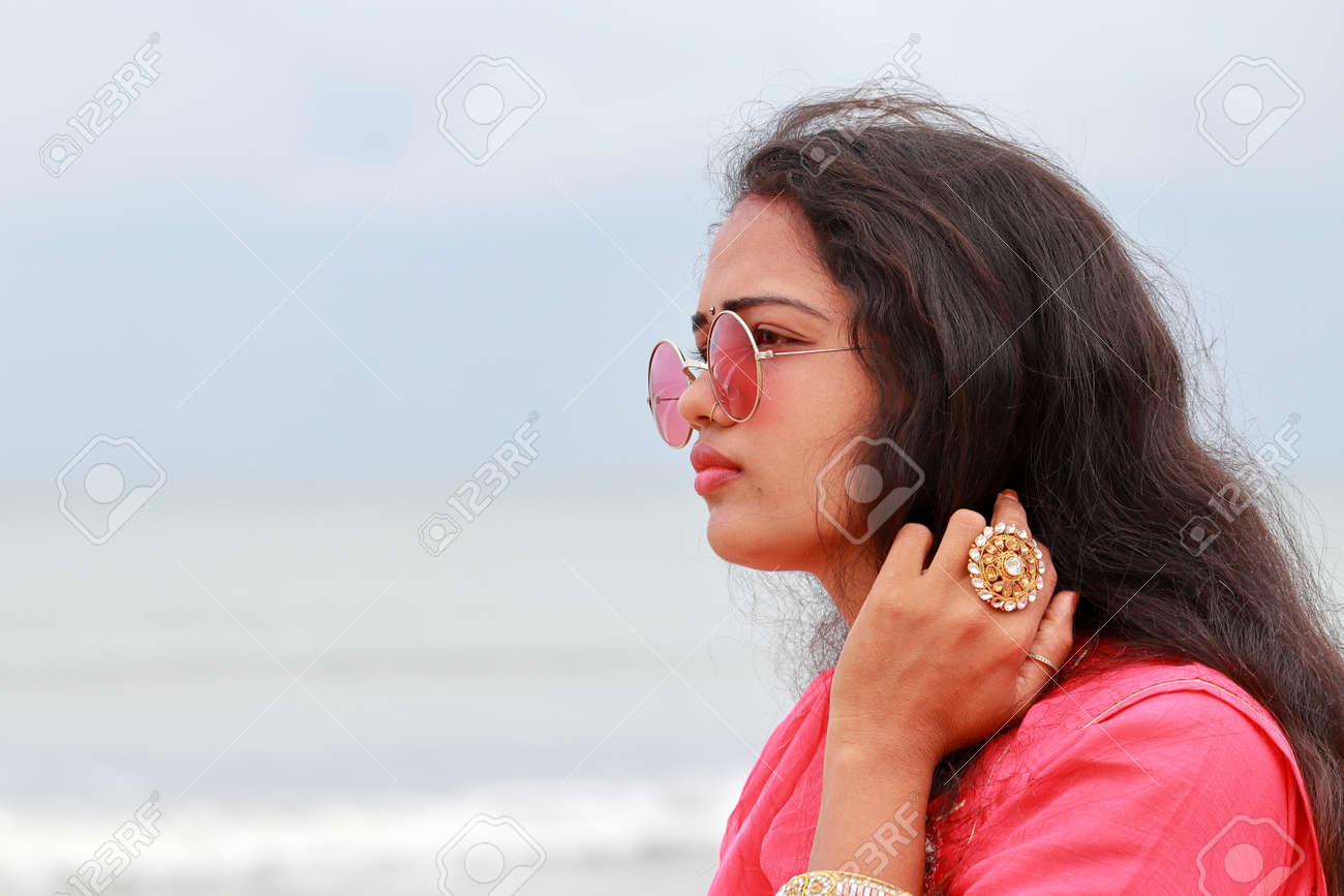 A portrait head shot of a beautiful young Indian woman standing alone on the shores of Chennai,And gorgeous lady models looking away and wearing their culture clothes, sunglasses and cosmetic apparel - 155981724