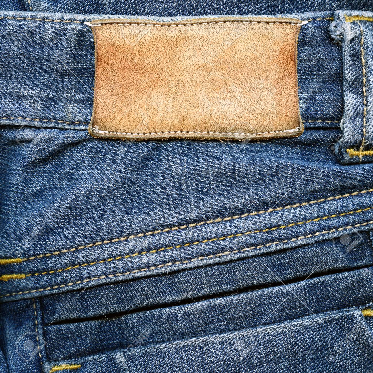 585761d54d29 Highly detailed closeup of blank grungy stained leather label on old blue  jeans with a lot