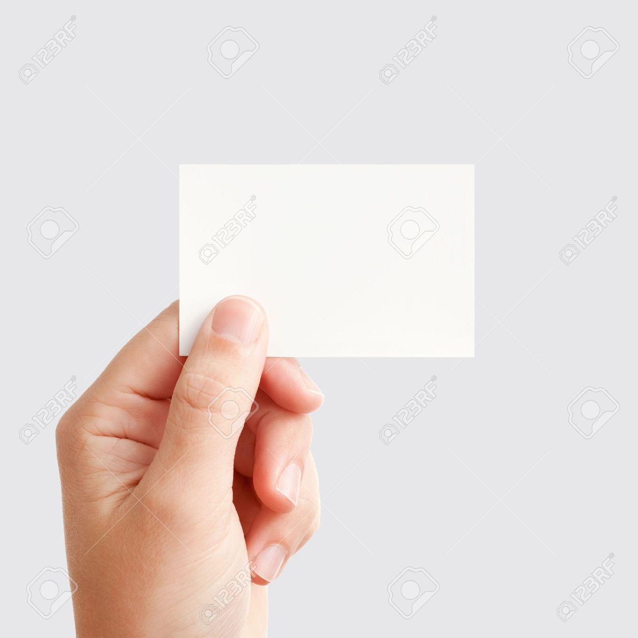 Businessman's hand holding blank white paper business card, closeup isolated on square gray background Stock Photo - 9078033