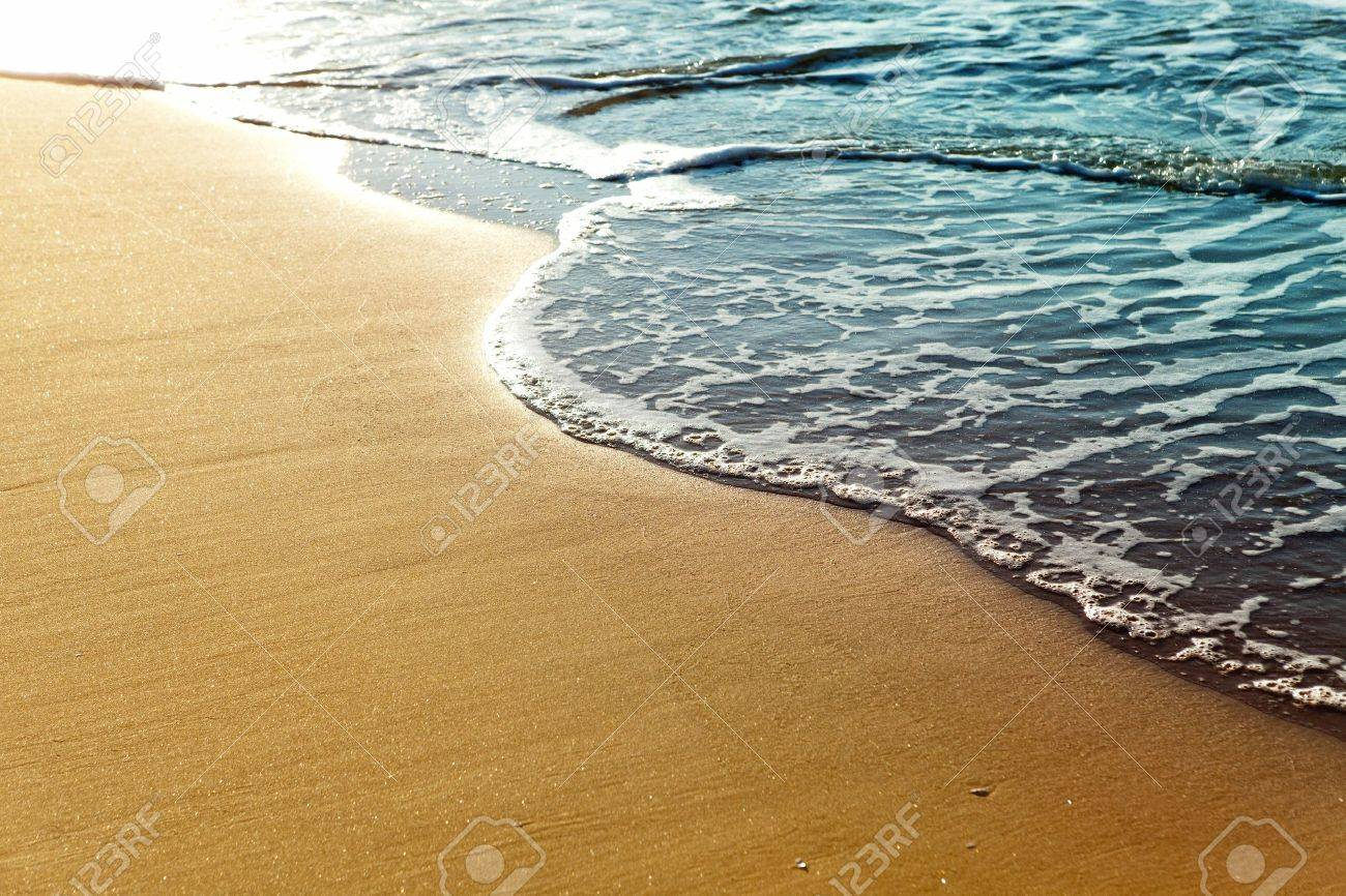 Shiny tropic sea wave on golden beach sand in sunset light Stock Photo - 10988938
