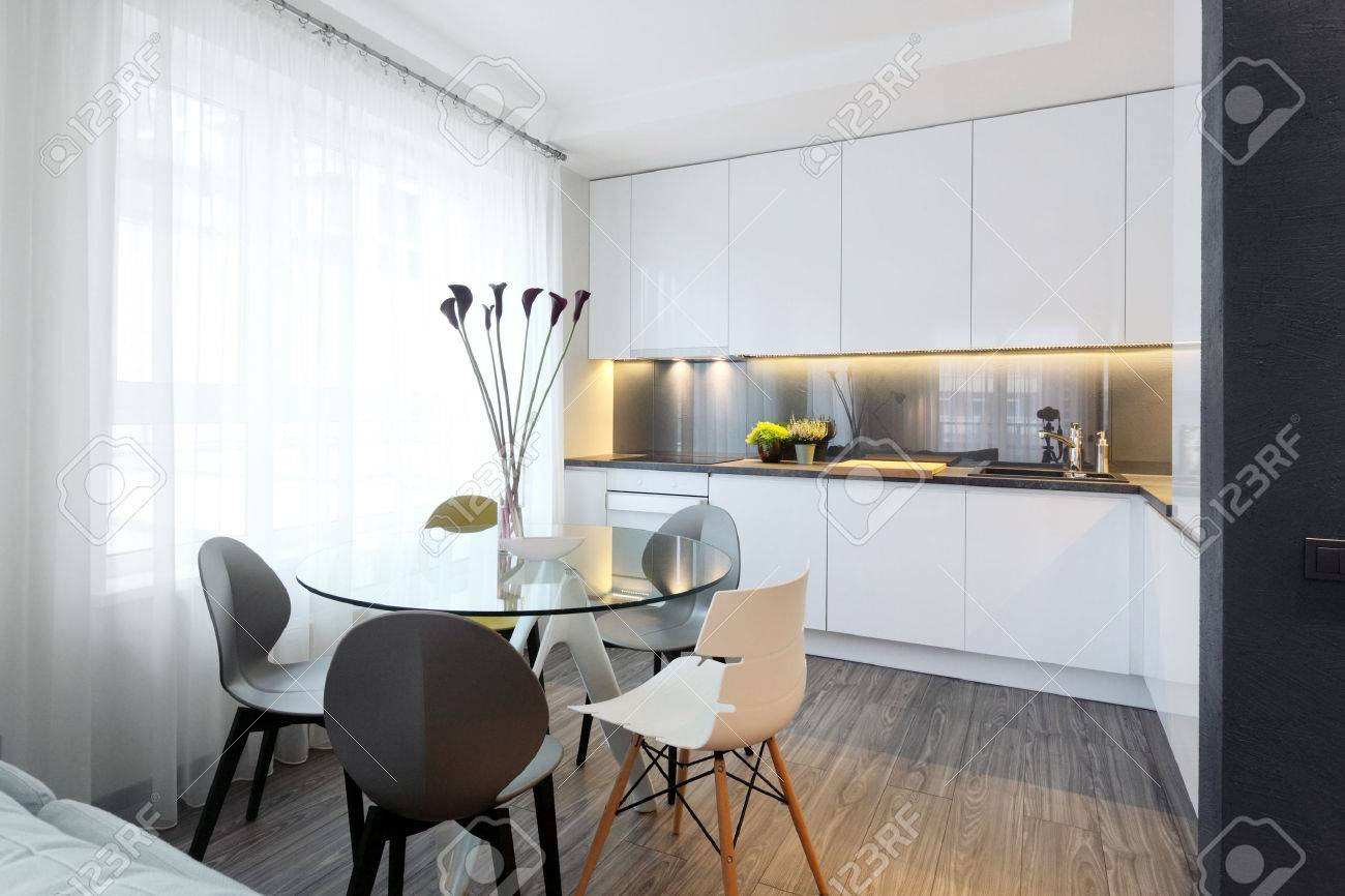 Interior White Modern Kitchen And A Glass Dining Table With