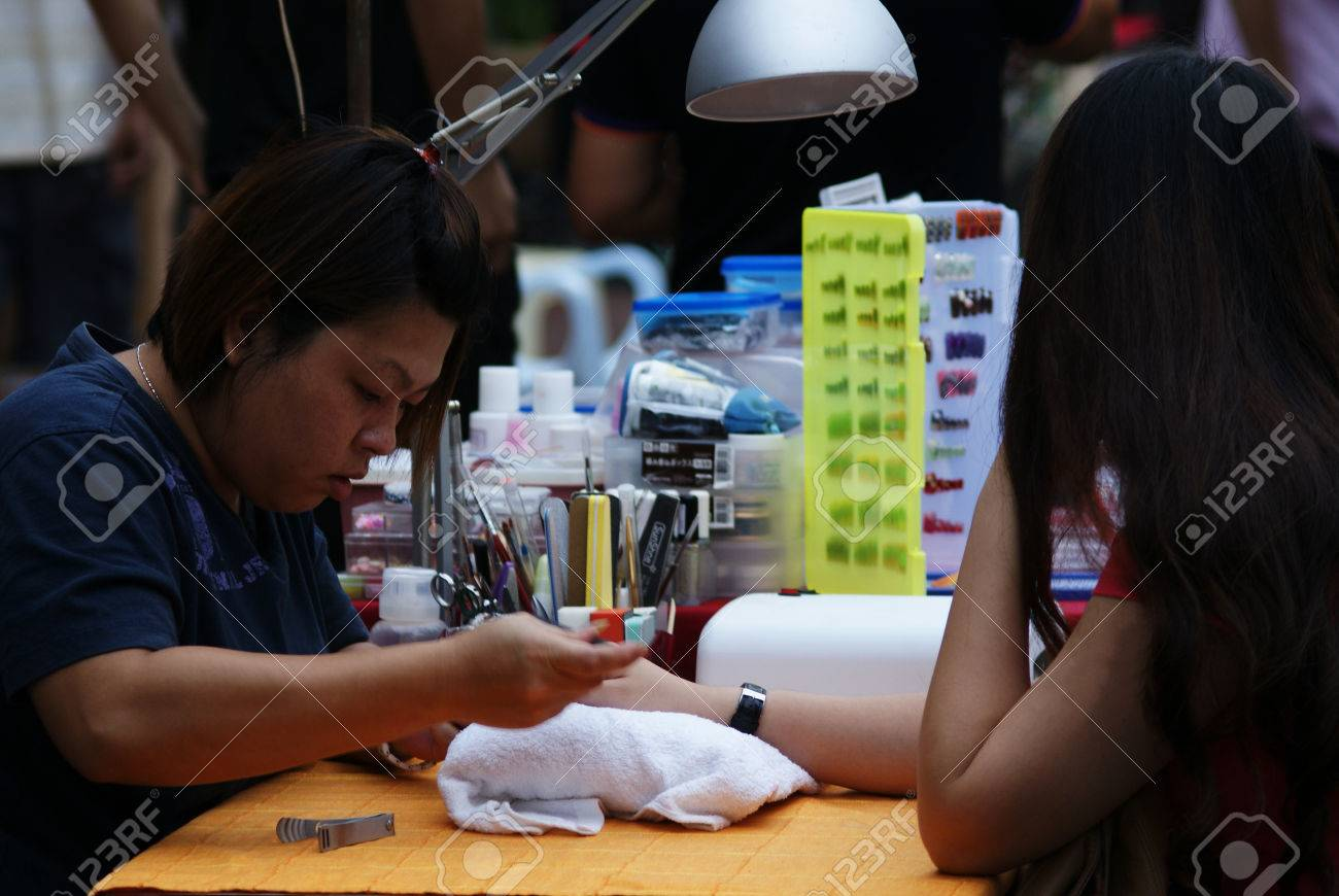 Asian Manicurist Lady Doing Manicure For A Customer At A Nail ...