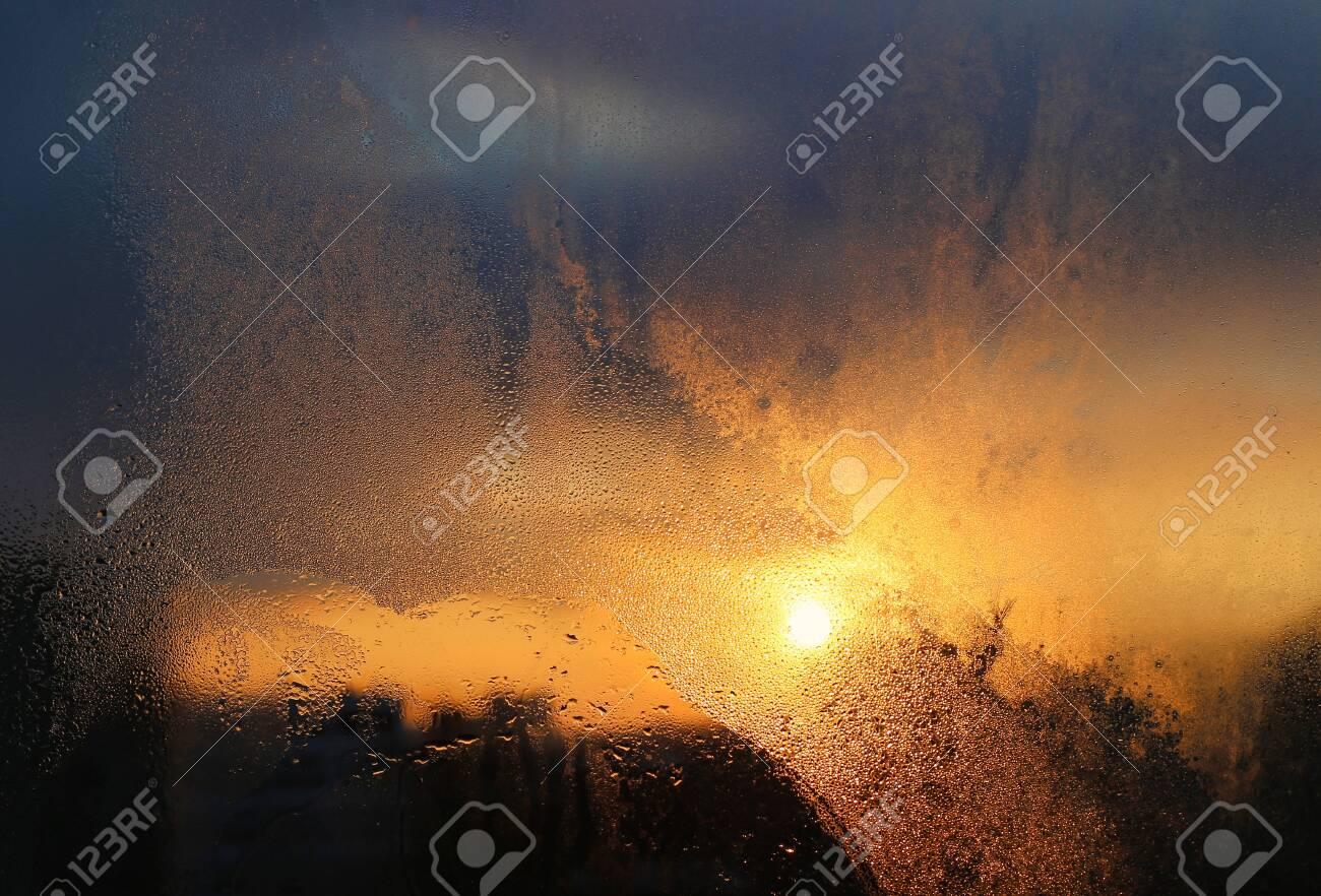 Melting ice, water drops and sunlight on a window pane in a winter morning, close-up natural texture - 133333346