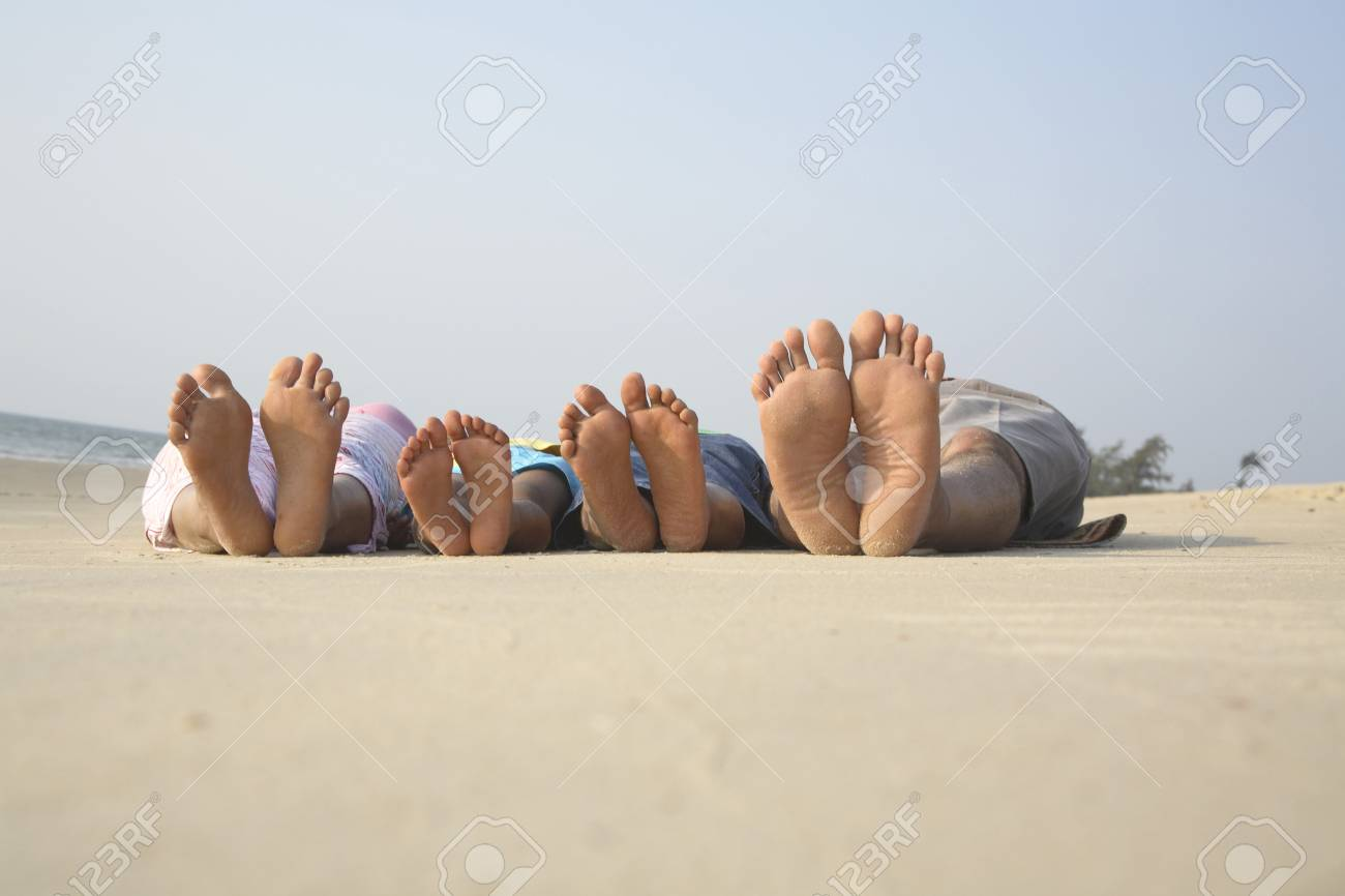 South Asian Indian parent and children showing barefoot sleeping on seashore facing sky - 85731660