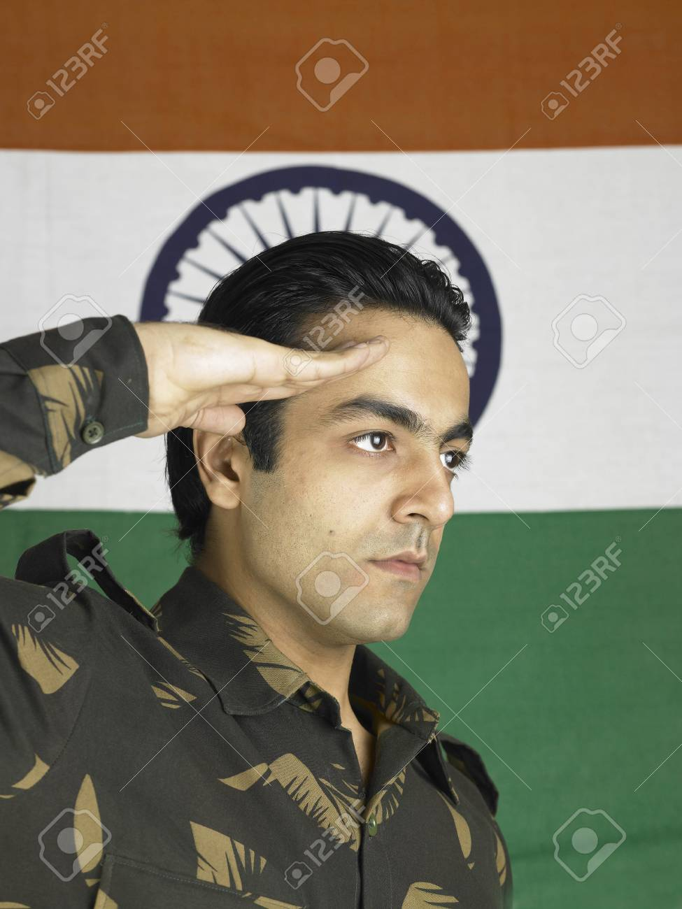 Indian Army Soldier Saluting Flag Of India In Background Stock Photo
