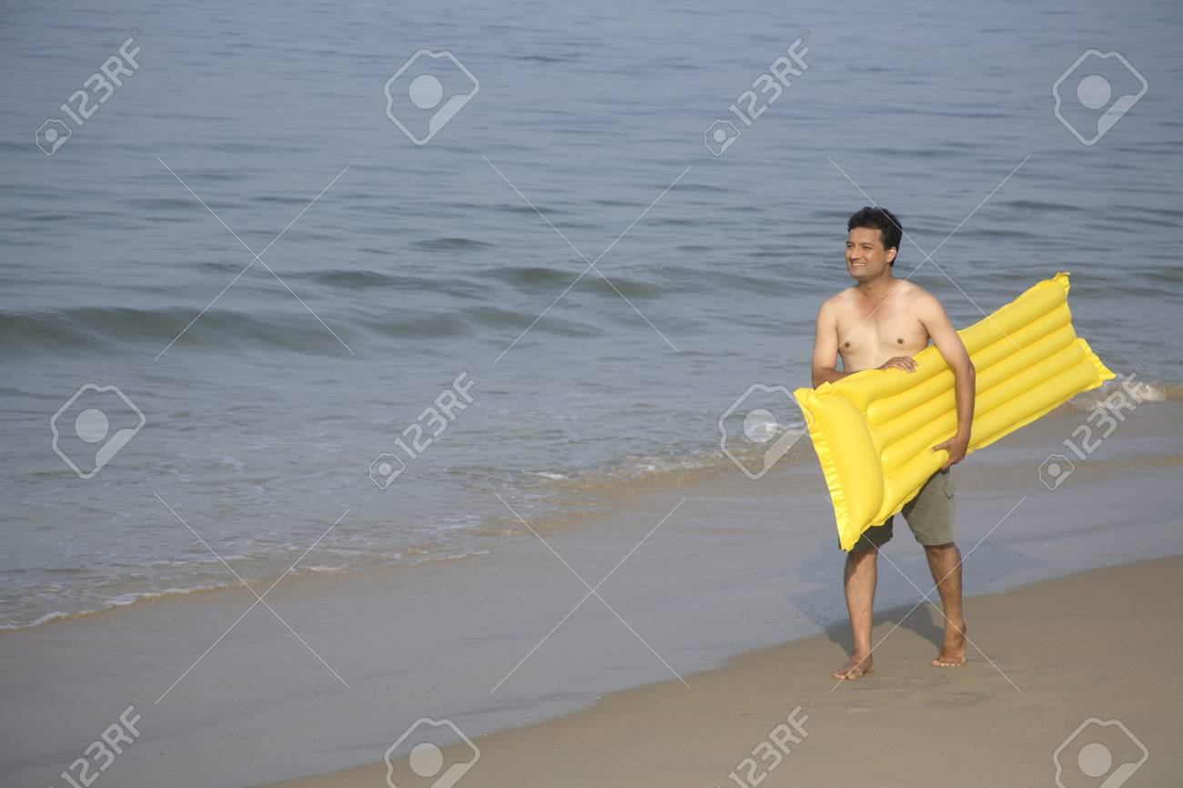 photo south asian indian young man holding yellow floating air bed in hand and walking on seashore shiroda