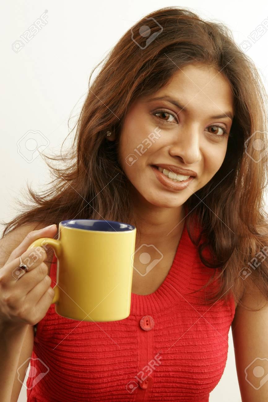 e3bae9f74273 Archivio Fotografico - Ragazza indiana asiatica del sud dell asiatico che  porta caffè superiore senza maniche rosso che gode del caffè in tazza gialla