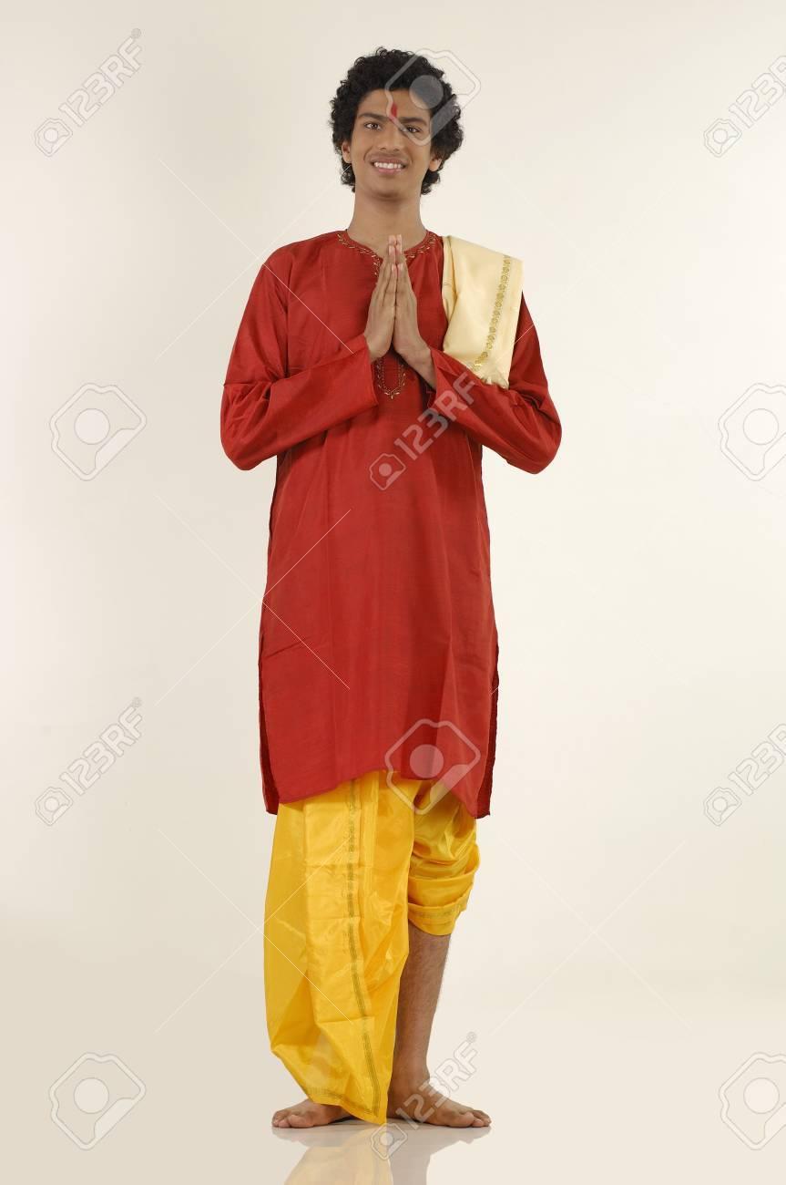f11a13fc28 South Asian Indian teenager boy wearing traditional yellow silk dhoti red  long kurta doing Namaskar,