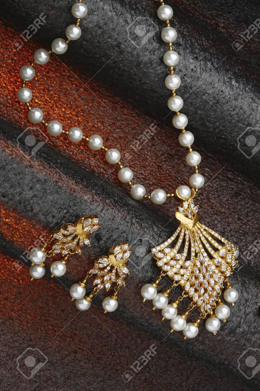 887889b3d2f2 Diamante collar de joyería de oro con diamantes y perlas orejas en el fondo  negro rojo