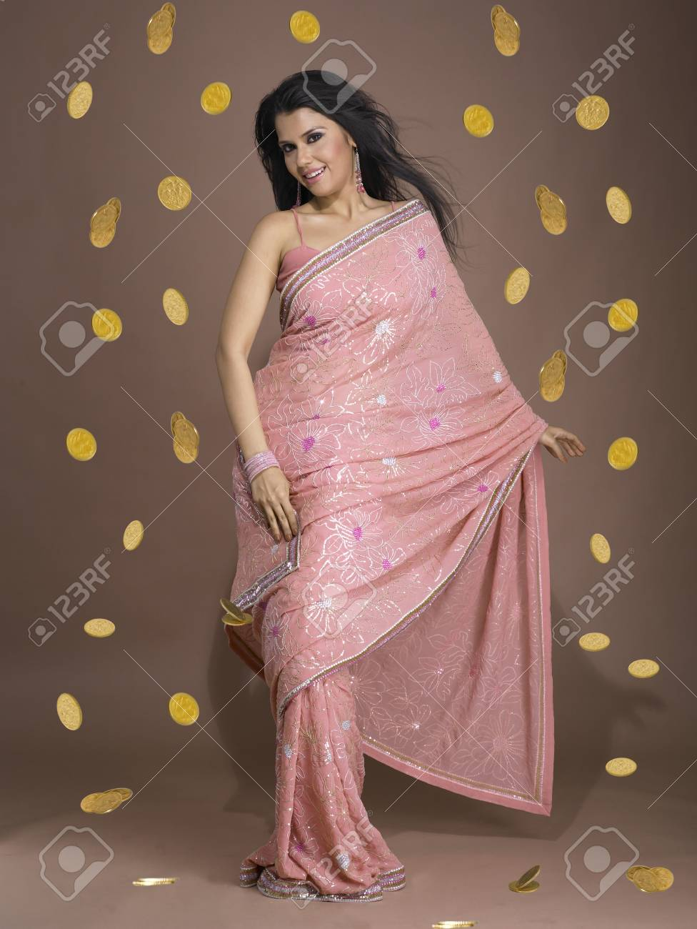 Girl In Sari With Shower Of Gold Coins All Around Her Stock Photo ...