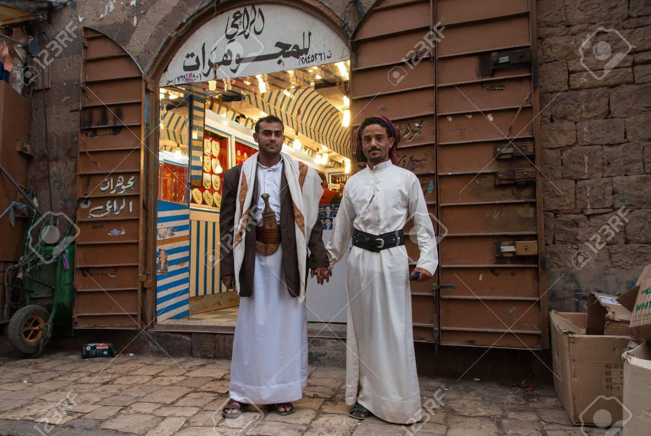 Sanaa, Yemen - May 4, 2007: Two men pose hand in hand in front of a jewellery store. Among other arabic countries, in 2012 Yemen became a site of civil conflicts. Stock Photo - 17378186