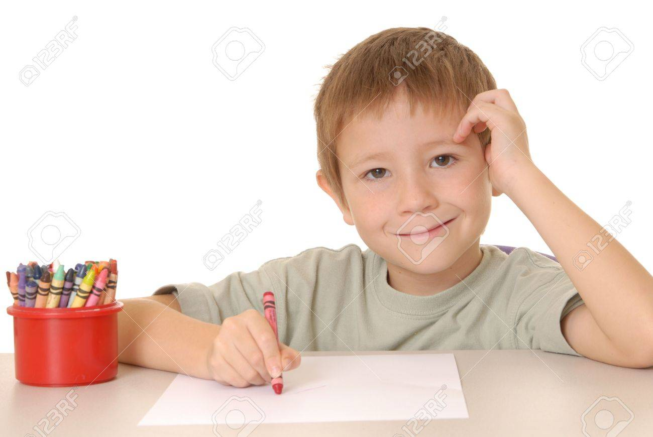 Young Boy Coloring A Sheet Of Paper With Crayon Stock Photo